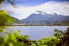 观看山和海滩在从灌木的海湾在山前面 免版税图库摄影
