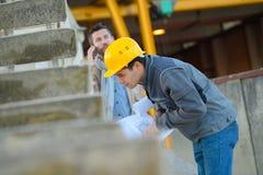 观看工作外面在建造场所的两名工作者 免版税库存照片
