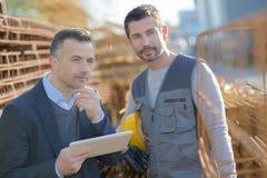 观看工作外面在建造场所的两名工作者 图库摄影