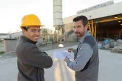观看工作外面在建造场所的两名工作者 免版税库存图片