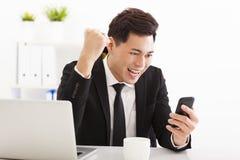 观看巧妙的电话的商人在办公室 库存照片
