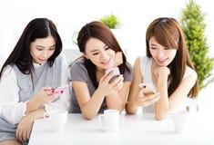 观看巧妙的电话的愉快的少妇在客厅 免版税库存照片