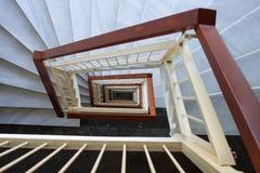 观看得下来成螺旋形与大理石步的楼梯,木路轨 免版税库存图片