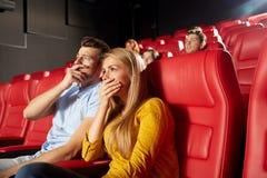 观看恐怖片的愉快的朋友在剧院 免版税图库摄影