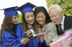 观看摄象机的两个毕业生和两个客人外面 免版税库存图片
