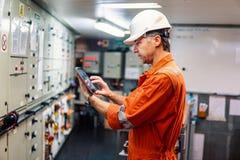 观看数字片剂的海洋总工程师在发动机控制室 免版税库存图片