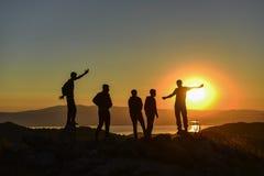 观看日出的人们在山顶 免版税库存照片