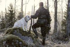 观看日出的猎人早晨在芬兰 他有一把猎枪在他的手和穿伪装制服 免版税图库摄影