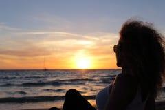 观看日落的妇女剪影在伊维萨岛 库存图片
