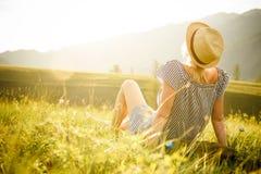 观看日落的妇女 平静和放松 免版税库存照片