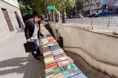 观看旧书的年轻人在室外跳蚤市场上 库存照片