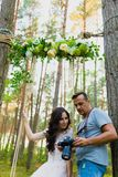 观看最近被拍的照片的摄影师和新娘 库存图片