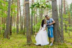 观看最近被拍的照片的摄影师和新娘 免版税库存照片