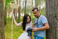 观看最近被拍的照片的摄影师和新娘 免版税库存图片