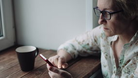 观看某事在智能手机屏幕上的妇女 股票录像