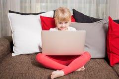 观看某事在计算机的小女孩 图库摄影