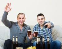 观看橄榄球用啤酒的两个人室内 库存图片