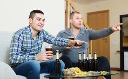 观看橄榄球用啤酒的两个人室内 免版税图库摄影