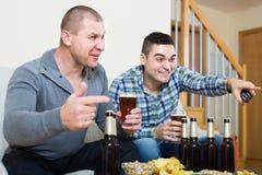 观看橄榄球用啤酒的两个人室内 库存照片