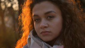 观看殷勤地和直接地入在晴朗秋季的照相机的相当卷发的白种人女孩特写镜头画象  库存图片