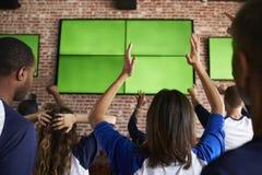 观看比赛的失望的朋友背面图在娱乐酒吧 免版税库存图片