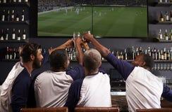 观看比赛的男性朋友背面图在娱乐酒吧 免版税图库摄影