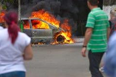 观看汽车的妇女和一个人燃烧在布加勒斯特 免版税库存照片