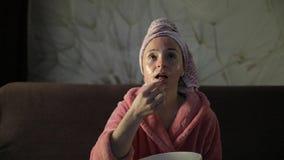 观看深夜电影的妇女在电视,吃玉米花 浴巾,面膜 影视素材