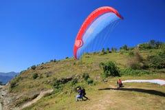 观看滑翔伞飞行的人们反对蓝天 免版税库存图片