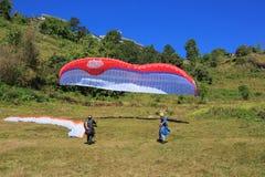 观看滑翔伞飞行的人们反对蓝天 库存照片