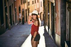观看照相机的可爱的女孩,当走在街道上时 免版税库存照片