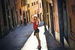观看照相机的可爱的女孩,当走在街道上时 免版税库存图片