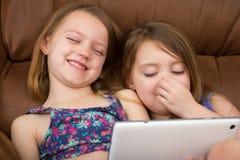 观看片剂和笑的两个女孩 库存图片