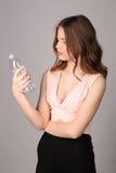 观看瓶水的女孩 关闭 灰色背景 库存图片