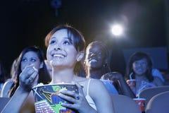 观看电影的微笑的妇女在剧院 库存图片