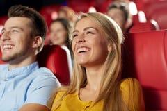 观看电影的愉快的朋友在剧院 库存图片