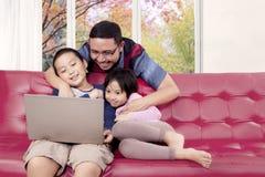年轻观看电影的父亲和他的孩子 免版税库存图片