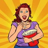 观看电影,微笑和吃玉米花的妇女 皇族释放例证