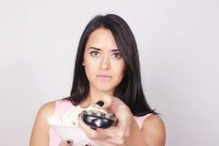 观看电影/电视的年轻白种人妇女 免版税图库摄影