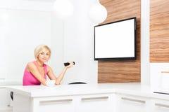 观看电视举行的妇女微笑遥控 免版税库存照片