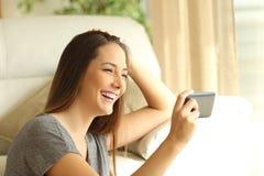 观看的女孩放出在一个巧妙的电话的录影 库存照片