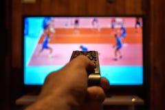 观看的电视和使用遥远的控制器 免版税库存图片