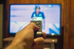 观看的电视和使用遥远的控制器 库存图片