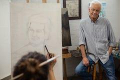观看的老人,当在帆布时的艺术家图画 免版税库存图片