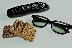 观看的televison的概念图象与3D玻璃和玉米花,快餐的 免版税库存照片