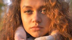观看直接地入照相机的相当卷发的白种人女孩特写镜头画象在秋季公园 免版税库存照片
