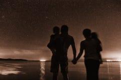 观看繁星之夜天空的家庭 库存图片