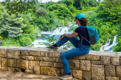 观看美丽的瀑布的女性远足者 免版税库存图片