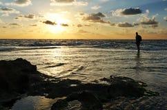 观看美好的海洋日落的人 免版税库存图片