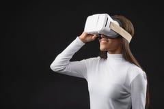 观看虚拟现实设备的愉快的非洲妇女 图库摄影